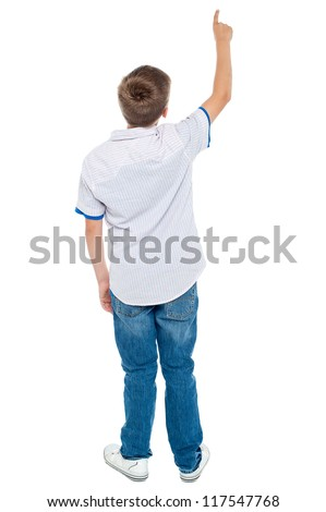 Rear view of a school boy over white background pointing upwards. Full length portrait