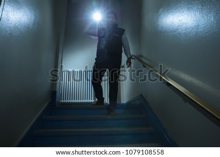 Rear View Of A Security Guard Standing Near Stairway Holding Flashlight #1079108558