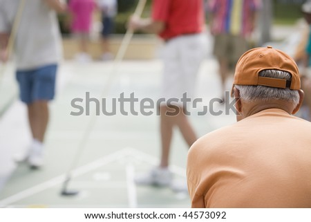 Rear view of a senior man playing shuffleboard