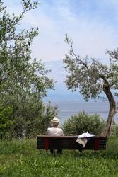 rear view of a senior man sits on the bench in front of lake Grada in Italy. The man's face can not be seen