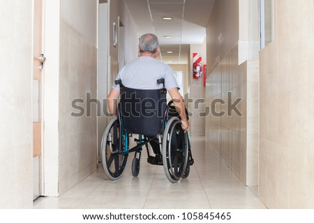 Rear view of a senior man sitting in a wheelchair at hospital corridor