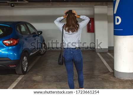 Rear View Of A Shocked Woman Standing In Parking Lot After her Car Was Stolen. Car missing. Woman returned after shopping and didn't find her car on underground parking Foto stock ©
