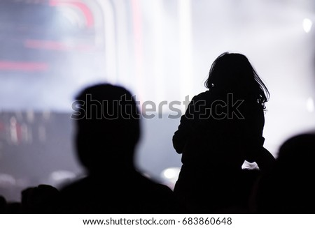 Rear view of a silhouette of a woman at concert. Bright stage lights in the background. Summer music festival concept #683860648