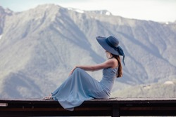 Rear view of a slim beautiful young woman in a hat sitting on a bench overlooking a gorgeous mountain landscape and admiring it on a sunny warm summer day while relaxing. Travel concept