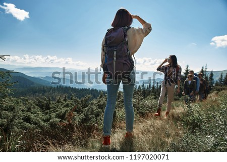 Rear view of a slim female tourist standing on the mountain hill while waiting for her friends