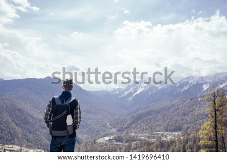 Rear view of a slim lonely young male traveler with a backpack reflexes and engaged in self-knowledge standing on the edge of a cliff overlooking a mountain forest valley
