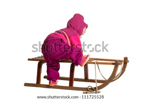 Rear view of a small toddler dressed in colorful winter woollies clambering onto a traditional wooden winter sled isolated on white