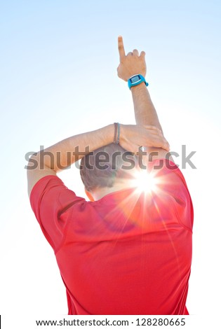 Rear view of a sports man wearing a red shirt and holding one arm up against a deep blue sky with sun rays filtering through his neck.