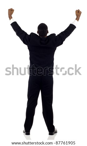 Rear view of a successful black business man with his arms up isolated white