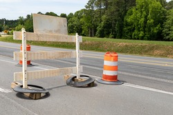 Rear view of a traffic barricade sign and orange and white traffic barrels, road closure, creative copy space, horizontal aspect