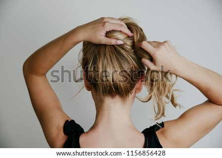 Rear view of a woman arranging her hair. Blond hair, tying hair in a bun. Woman on a light gray background. The concept of hairdressing, hair styling.