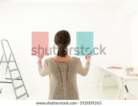 Rear view of a woman choosing colour for painting a room against white background