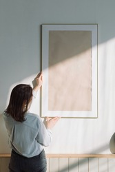 Rear view of a woman hanging a large poster frame on the wall in a modern apartment.