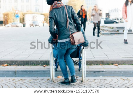 rear view of a woman helping a disabled person to go down the steps with the wheelchair - architectural boundaries in the cities concept #1551137570