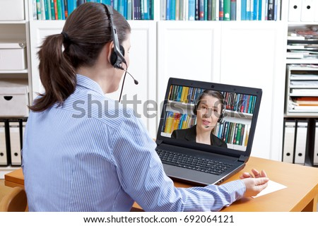Rear view of a woman in a blue blouse with headset and laptop, having a live video call with her friendly attorney, solicitor or lawyer, online legal advice concept
