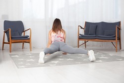 Rear view of a woman in grey leggings in Surya Namaskara in a home interior.