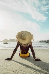 Rear view of a woman relaxing on beach. African female model in bikini wearing a straw hat on sea shore. Woman on beach vacation.