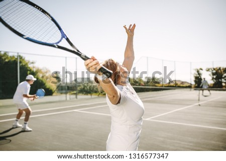Rear view of a woman serving the ball while playing a mixed doubles tennis match. Men and women playing tennis outdoors on a sunny day.