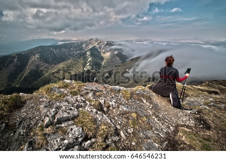 Rear view of a woman sitting on a mountain top peacefully gazing at low-lying  clouds. HDR image. - Shutterstock ID 646546231