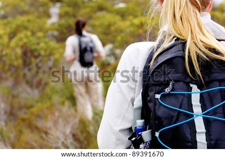 rear view of a woman trekking outdoors with a backpack