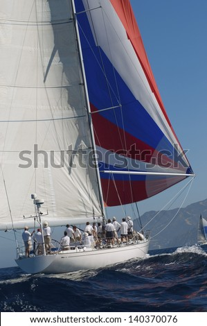 Rear view of a yacht in the ocean with full sail against the clear sky