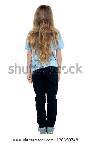 Rear view of a young blonde girl with long hair, full length portrait.