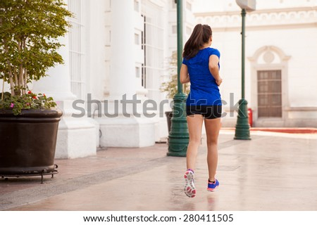Rear view of a young brunette in a sporty outfit exercising in the city #280411505