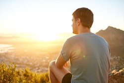 Rear view of a young guy resting on a nature trail watching the sunrise