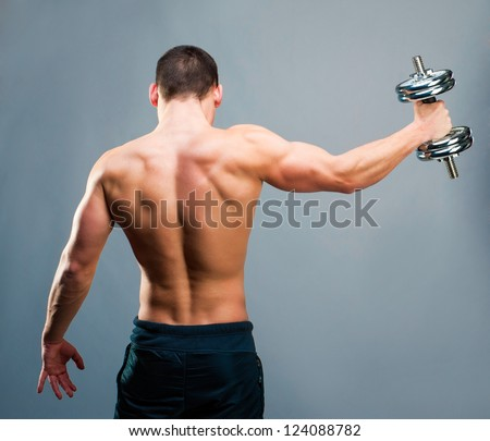 Rear view of a young male bodybuilder doing heavy weight exercise with dumbbells against gray backg