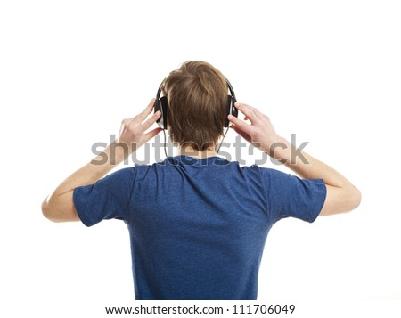 Rear view of a young man listening music with headphones, isolated on white background