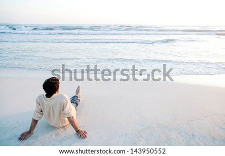 Rear view of a young man sitting on a white sand beach during sunset contemplating the scenery and the blue sea waves during his vacation in an idyllic nature scene destination.