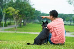 Rear view of a young man sitting on the grass and showing something to his dog