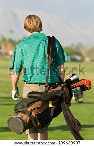 Rear view of a young man walks with a golf bag on shoulder