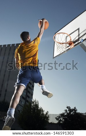 Rear view of a young man with basketball jumping towards hoop