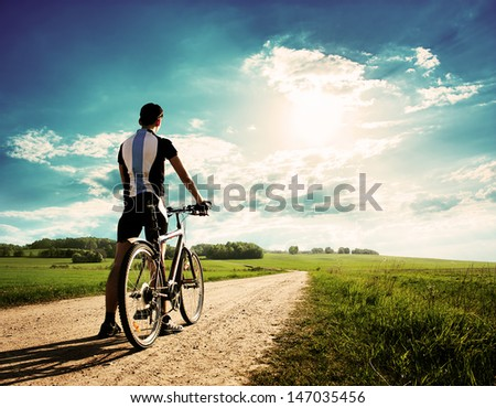 Rear View of a Young Man With Bicycle on Summer Nature Background. Healthy Lifestyle Concept. Copyspace.