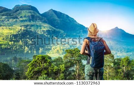 Rear view of a young tourist girl enjoying amazing beauty of tropical nature of Nuwara Eliya, Sri Lanka, active summer vacation on exotic island