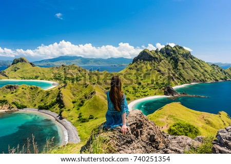 Rear view of a young woman enjoying the awesome view of Padar Island, while sitting on the top of a volcanic mountain during summer vacation in Indonesia
