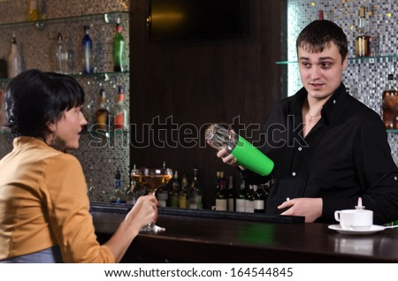 Rear view of a young woman having drink bar while talking barman in a fancy location - stock photo
