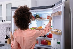 Rear View Of A Young Woman Taking Food To Eat From Refrigerator