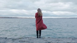 Rear view of a young woman wearing a red coat against a bright blue sky and sea on a holiday beach, outdoors. Rear view of alone young adult girl standing on the beach, looking to sea. Travel and