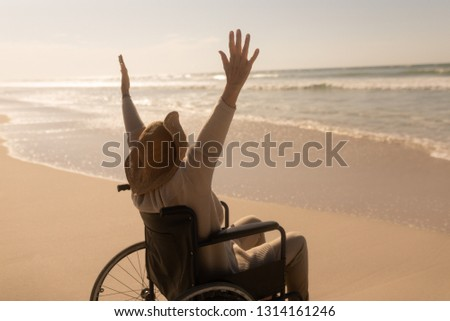 Rear view of active disabled senior woman with arms up on the beach