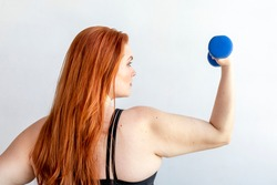 Rear view of active woman with dumbbell
