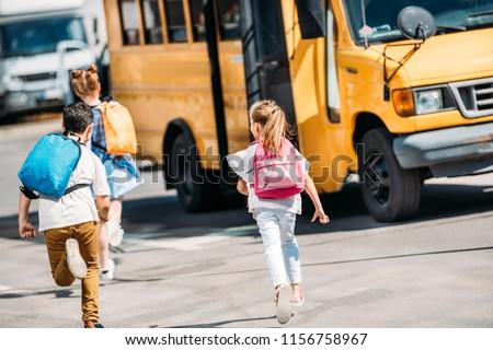 rear view of adorable schoolchildren running to school bus