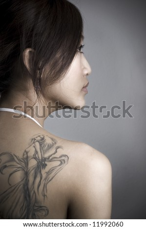 stock photo : rear view of adult woman with tattoo, low key.