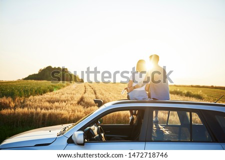 Rear view of affectionate couple catching a break during road trip