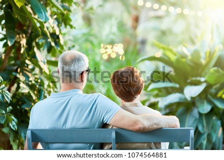 Rear view of affectionate senior couple sitting on bench in the garden or park at leisure