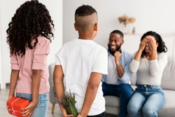 Rear view of African American children making surprise for their parents, hiding present and flowers behind back, greeting woman with Mother's day. Lady covering eyes sitting on couch in living room