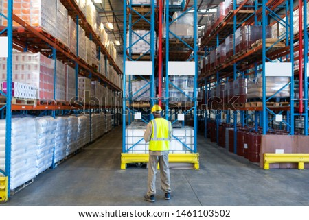 Rear view of African-american male worker working in warehouse. This is a freight transportation and distribution warehouse. Industrial and industrial workers concept #1461103502