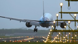 Rear view of aircraft landing at Schiphol airport at rainy weather. Shot from the beginning of runway. Landing lights at the foreground.