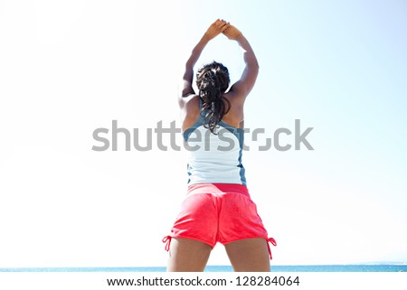 """Rear view of an """"african american"""" woman stretching her arms and back while standing against a deep blue sky, exercising on a sunny day."""